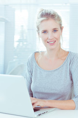 Blond haired woman using her laptop