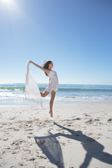 Attractive woman jumping with sarong