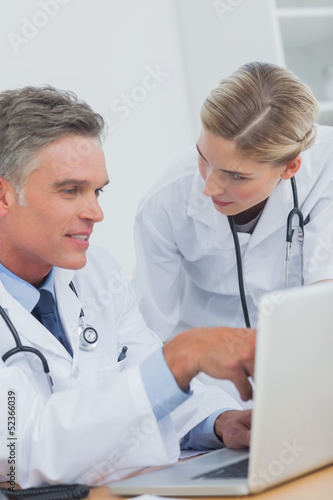 Smiling doctor pointing at a laptop