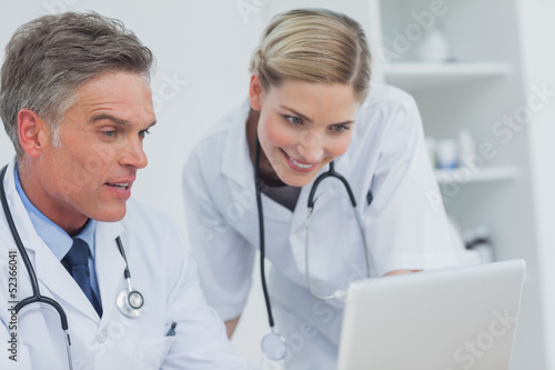 Two doctors watching a laptop