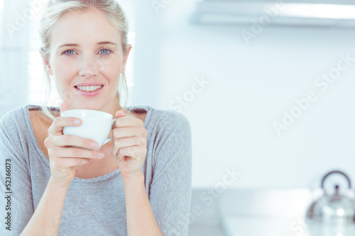 Radiant woman drinking a cup of tea