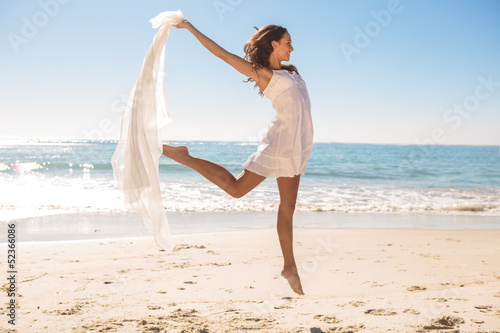 Attractive woman jumping on the beach