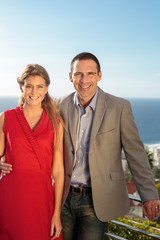 Couple gesturing in front of the camera on balcony