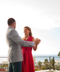 Lovely couple dancing together on the balcony