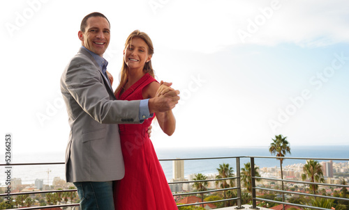 Delighted couple dancing on the balcony