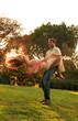 Man revolving girlfriend in a park while he is holding her