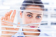Delighted businesswoman peeking through a venetian blind