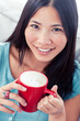 Smiling asian woman holding a cup of coffee