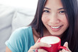 Pretty asian woman holding a mug of coffee
