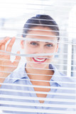 Cheerful businesswoman smiling through venetian blind