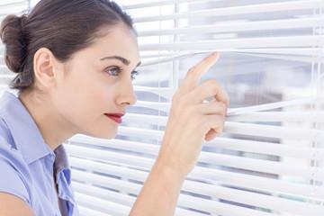 Pretty businesswoman peeking through a venetian blind