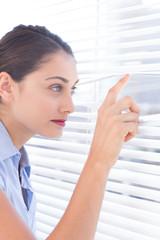 Brunette businesswoman peeking through a roller-blind