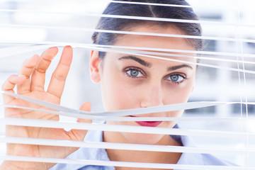 Delighted businesswoman peeking through a venetian blind