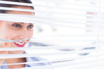 Beautiful businesswoman peeking through venetian blind