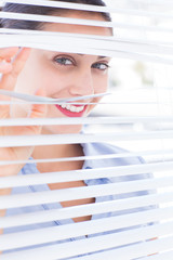 Attractive businesswoman looking through a venetian blind