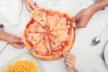 Hands taking slice of pizzas