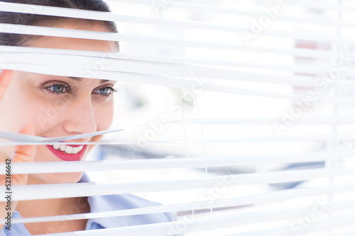 Beautiful businesswoman peeking through venetian blind