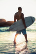 Attractive surfer walking in the sea