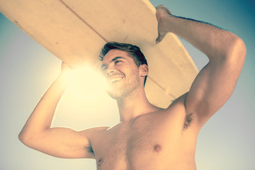 Handsome man holding his surfboard above his head