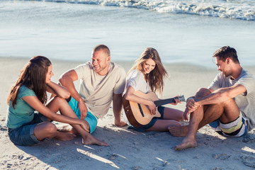 Friends sitting on the sand playing guitar