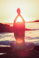 Silhouette of woman doing yoga during the sunset