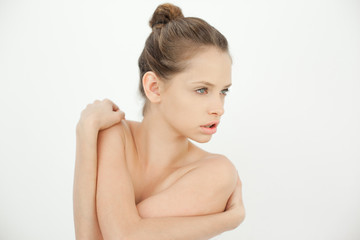 Attractive topless woman holding her shoulders