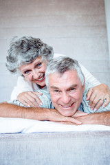 Mature couple cuddling and lying together