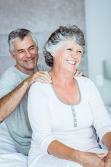 Mature man giving a shoulders massage to his wife