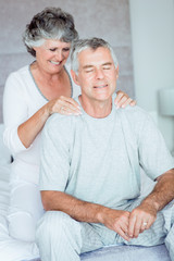 Mature woman giving a shoulder massage to her husband