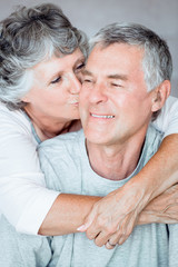 Cheerful mature woman kissing her husband