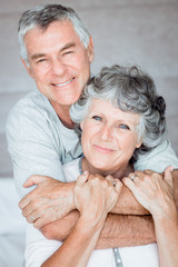 Cheerful retired couple posing together on the bed