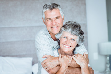 Retired couple posing together on the bed