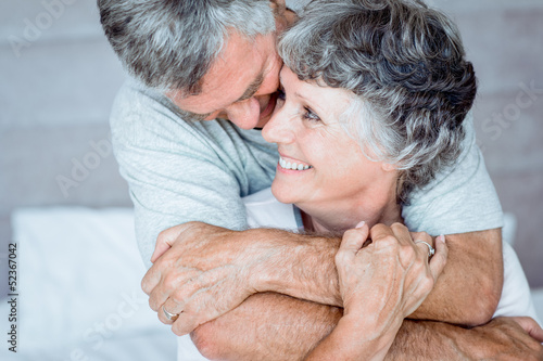 Mature man cuddling his wife