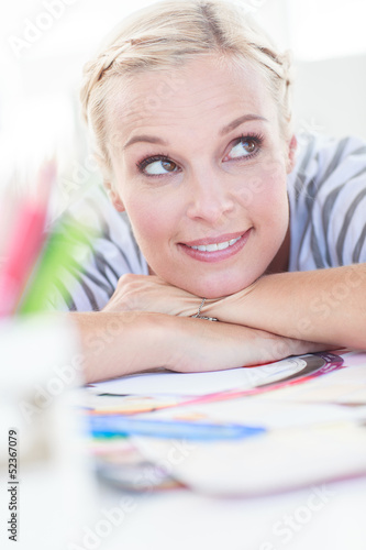 Happy designer posing on her desk