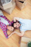 Young couple lying on the wooden floor