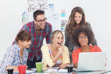Cheerful team of creative designers working on a laptop