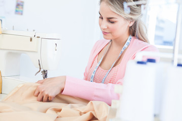 Pretty fashion designer sewing a textile