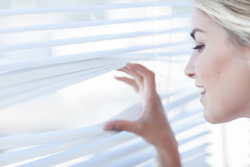 Blonde woman peeking through venetian blinds