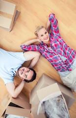 Couple lying on the wooden floor