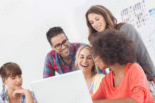 Happy team of creative designers working on a laptop