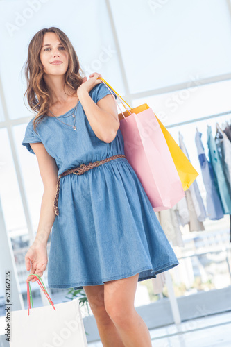 Pretty brunette holding shopping bags