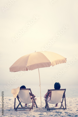 People relaxing on the beach reclining on deck chairs