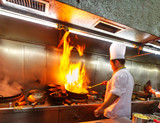Chef in restaurant kitchenm, doing flambe on food - 52368846