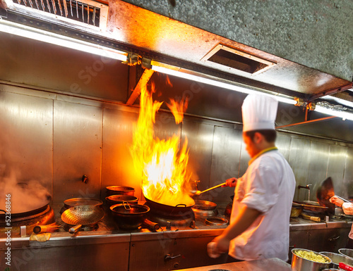 Chef in restaurant kitchenm, doing flambe on food