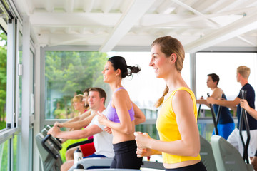 People in sport gym on treadmill running