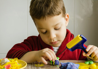 Cute child playing with plasticine