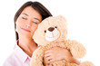 Woman daydreaming with a teddy bear
