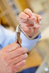Hand mit Zange repariert Brille