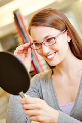 Frau mit Brille schaut in Spiegel
