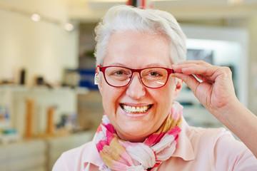 Seniorin mit Brille beim Optiker